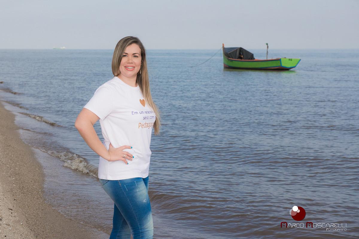 Ensaio da formanda Andressa Bastos na ilha da Feitoria. Formanda posando com a lagoa ao fundo e embarcação de pescadores nas cores verde e laranja. Foto por Marco Moscarelli.