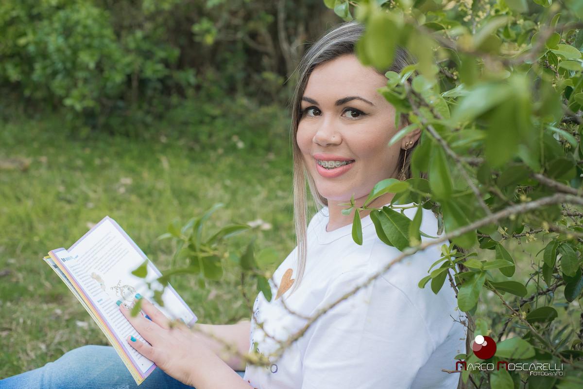 Ensaio da formanda Andressa Bastos na ilha da Feitoria. Formanda posando entre os arbustos lendo um livro e com lindo sorriso no rosto.  Foto por Marco Moscarelli.