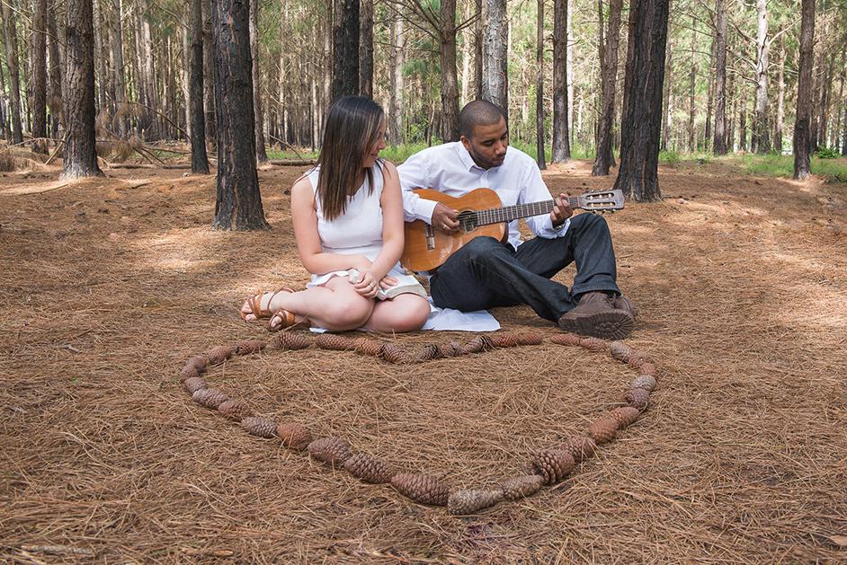 Foto do ensaio do casal, noivo tocando violão para a noiva em um bosque com um coração de pinhas ao chão.