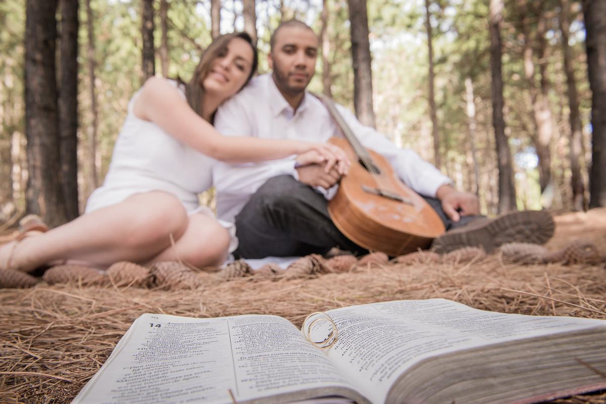 Casal de noivos posando para foto em bosque com a biblila e alianças compondo a cena.
