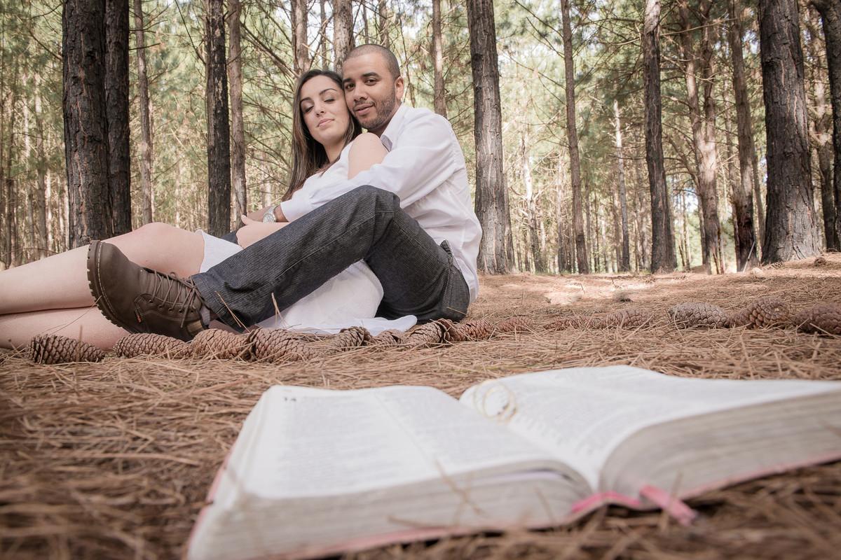 Casal de noivos posando para foto em lindo bosque com a biblia e as aliças compondo a cena.