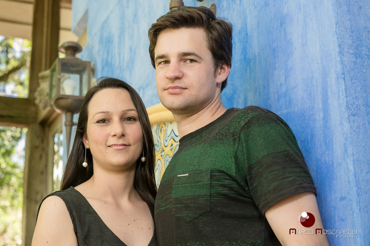 Casal de noivos posando para fotos do ensaio pré - weding em uma parede azul na charqueada santa rita.