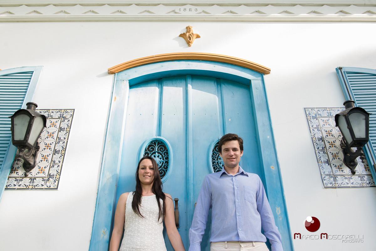 Noivos em ensaio pré wedding, posando com portas e janelas azuis de casa antiga. fotos de casamento por Marco Moscarelli