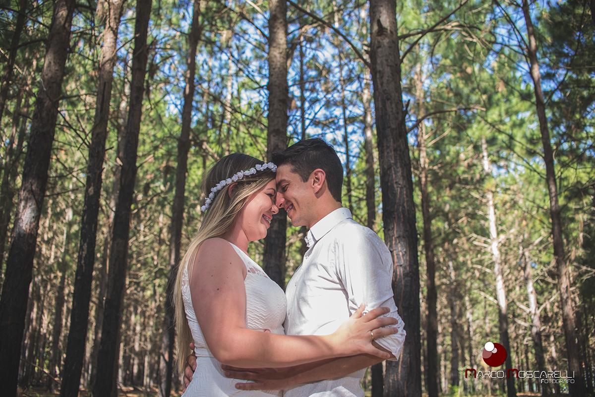 Noivos de rosto colado em ensaio pré-wedding com arvorees e um lindo céu azul de fundo.