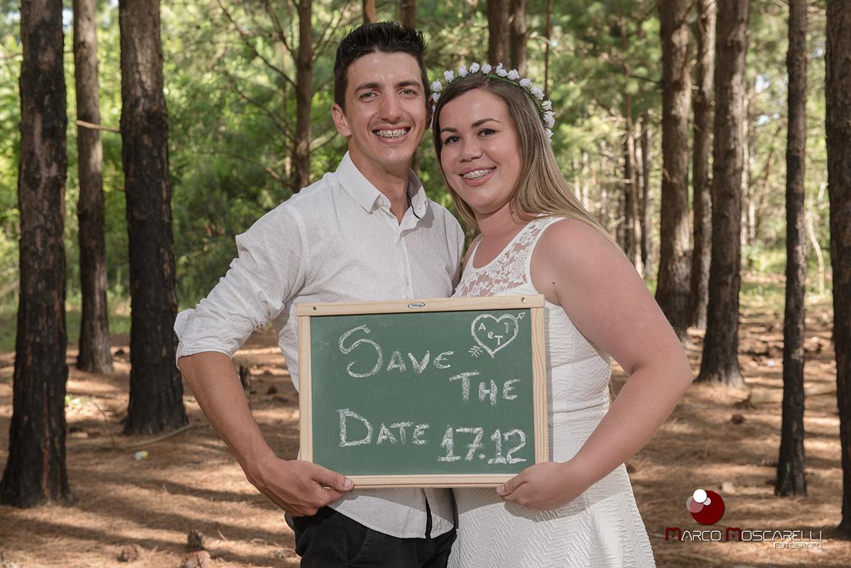 Noivos segurando quadro com o save the date do casamento durante ensaio pré wedding. Foto por Marco Moscarelli.
