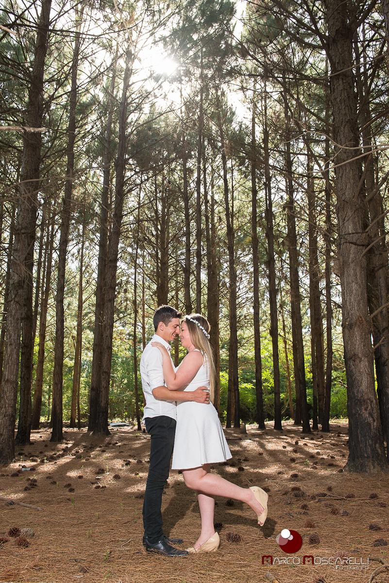 Noivo e noiva de rosto colado com lindo bosque de acacias ao fundo em ensaio pré-wedding. Foto por Marco Moscarelli