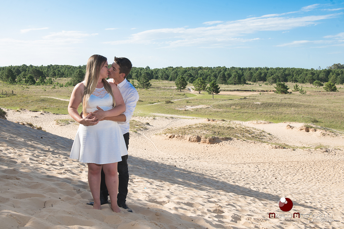 Casal de noivos posando abraçados no alto de uma duna de areia com um lindo bosque de acácias ao fundo em ensaio pré-wedding. Foto por Marco Moscarelli
