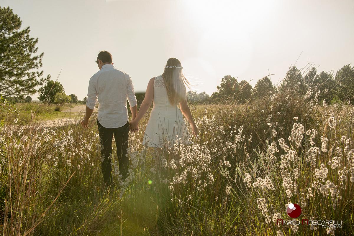 Casal de noivos caminhando no por do sol em um lindo campo acariciando a vegetação durante ensaio pré-wedding. Foto por Marco Moscarelli