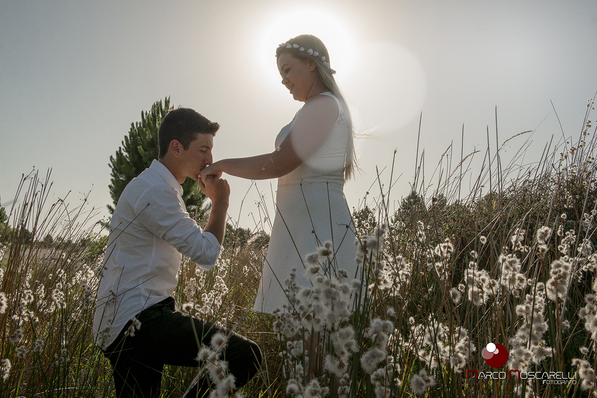 Noivo beijnado a mão da noiva em um campo  durante o por do sol durante ensaio pré-wedding. Foto por Marco Moscarelli