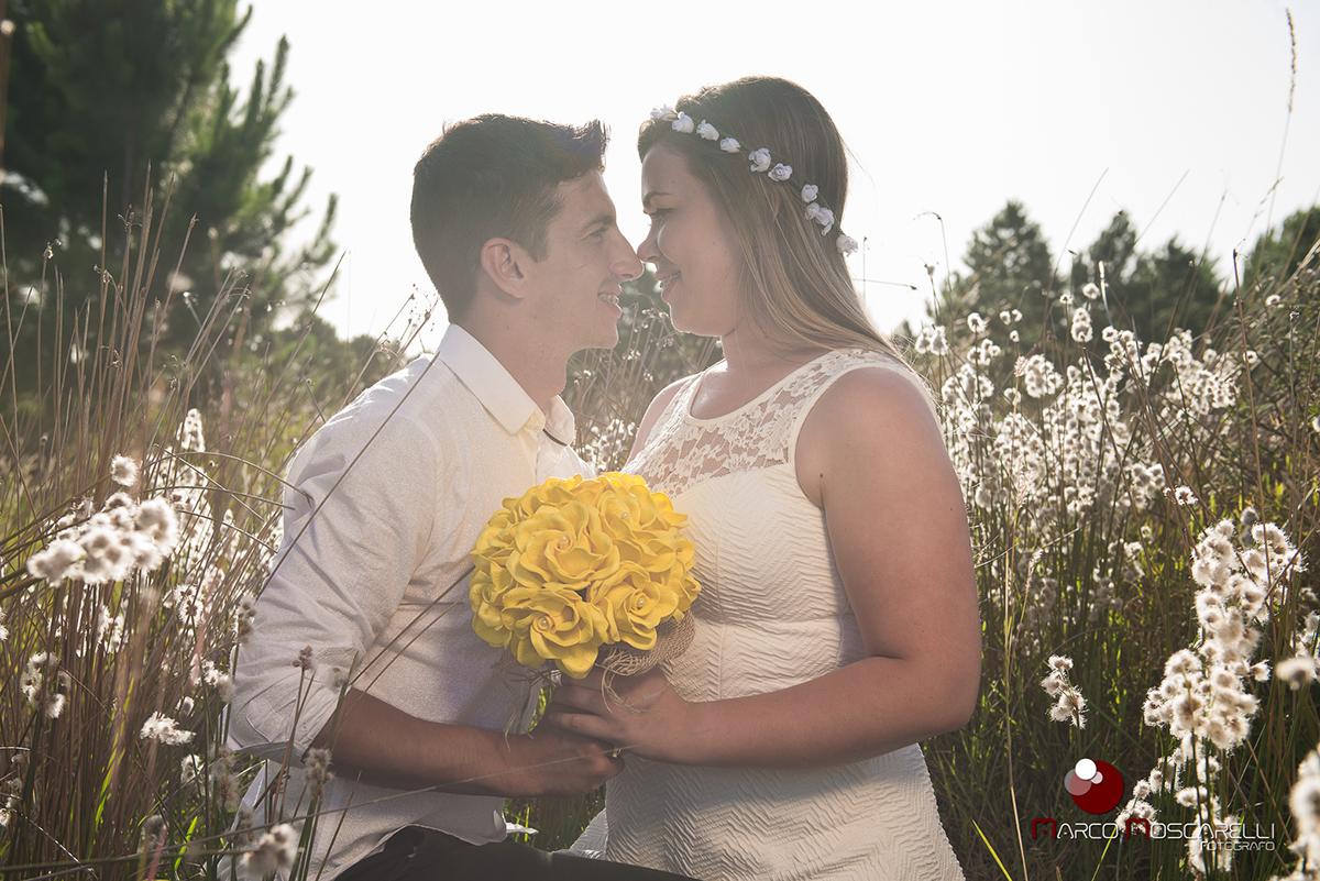 casal de noivos trocando olhares em um lindo campo florido durante por do sol em ensaio pré wedding. Foto por Marco Moscarelli