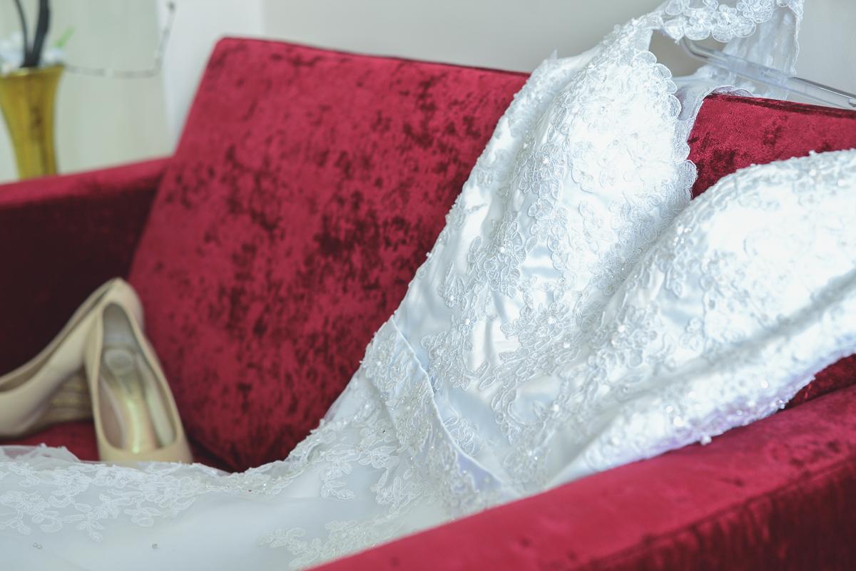 Vestido da noiva descançando sobre um sofá vermelho durante make da noiva