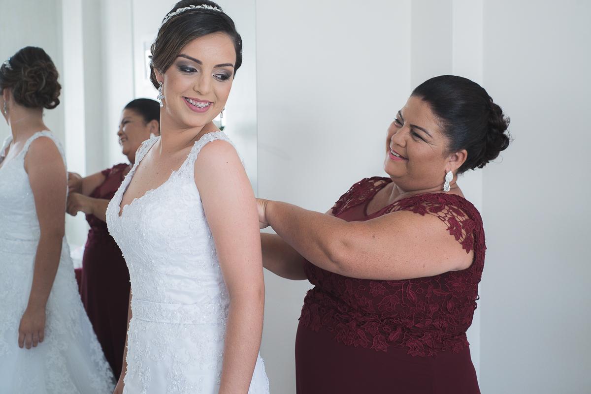 Mae da noiva ajustando o vestido antes da cerimonia de casamento