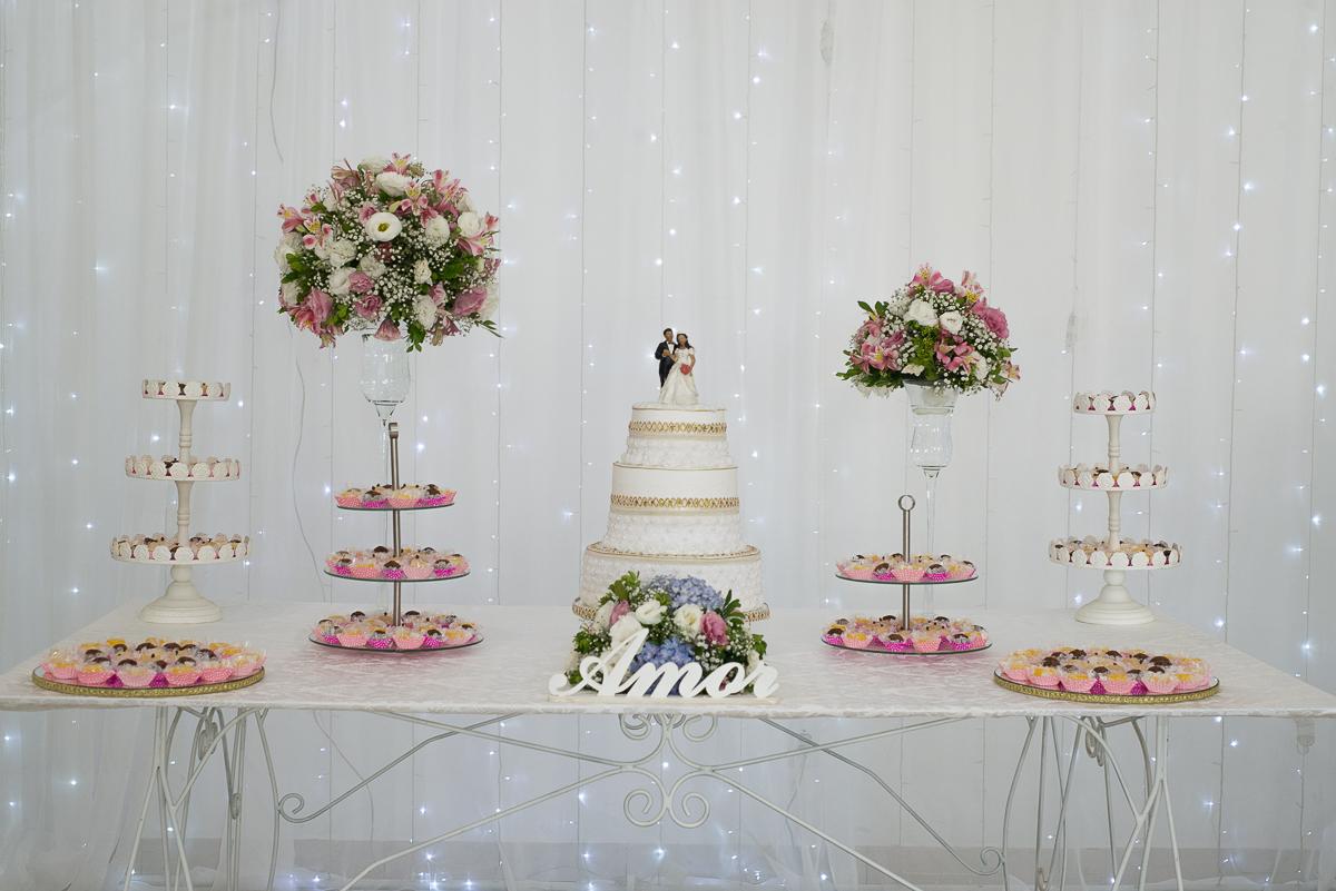 Foto da mesa do bolo dos noivos que compões a decoração da recepção de casamento