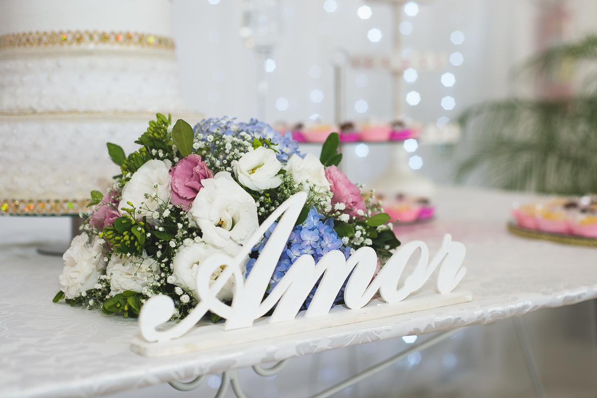 detalhe da decoração da mesa dos noivos. Amor escrito em madeira na cor branca.