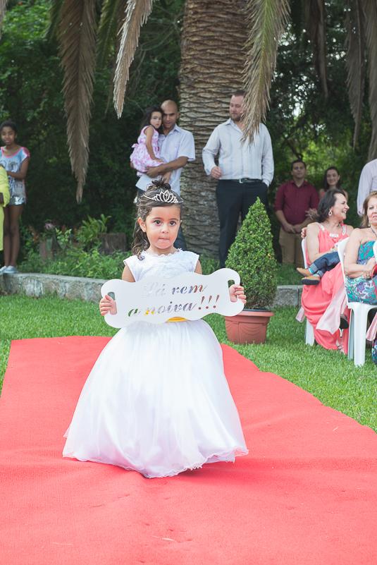Aia entrando no tapete vermelho do casamento segurando plaquinha decorativa la vem a noiva.
