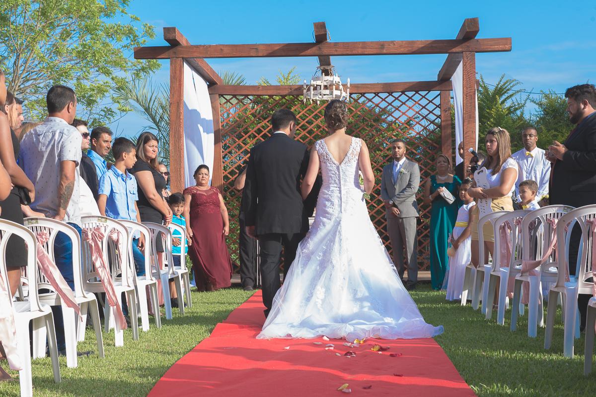 Noiva fotografada de costas indo em direção ao altar do casamento