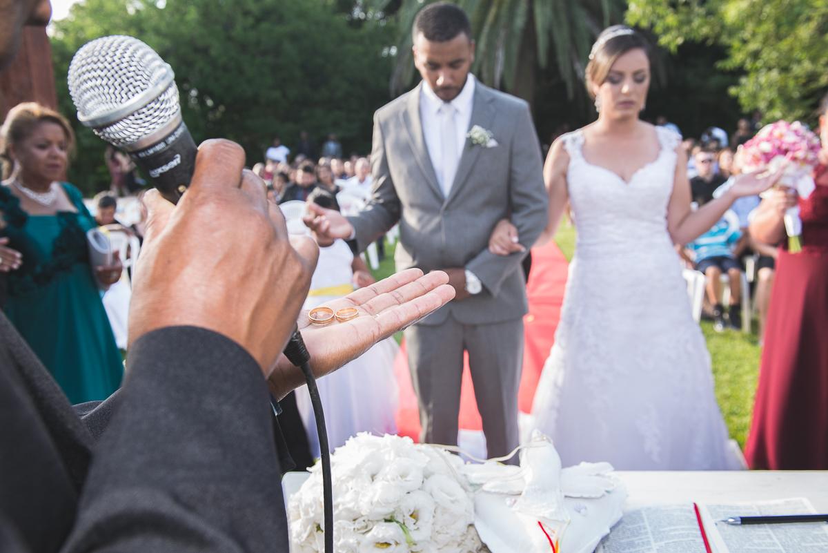 Padre abençoando as alianças dos noivos durante o casamento.