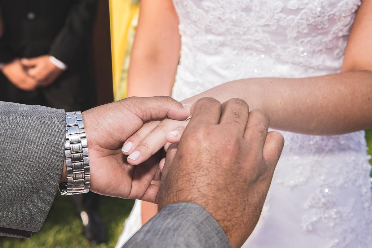 Noivo colocando aliança no dedo da noiva.