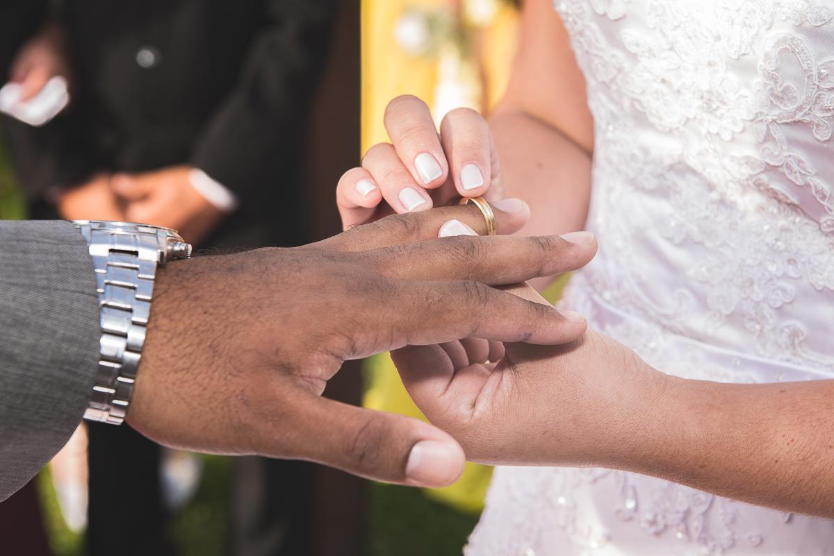 Noiva colocando aliança no dedo do noivo.