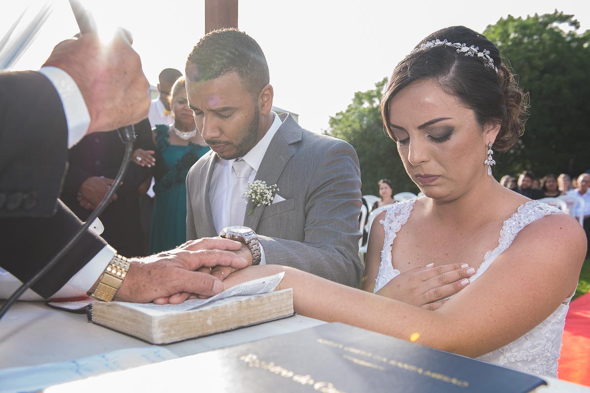 Noivos ajoelhados no altar e padre abençoando as mãos dadas dos noivos.
