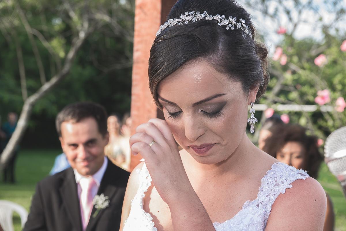 Noiva enchugando uma lagrima no seu rosto durante a cerimônia de casamento.