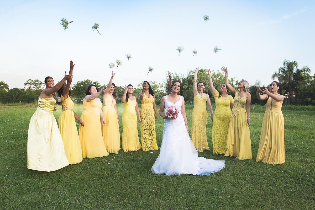 Noiva posando com as madrinhas que jogam flores para o alto.
