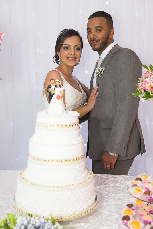 Noivos posando para fotos atras do bolo de casamento.