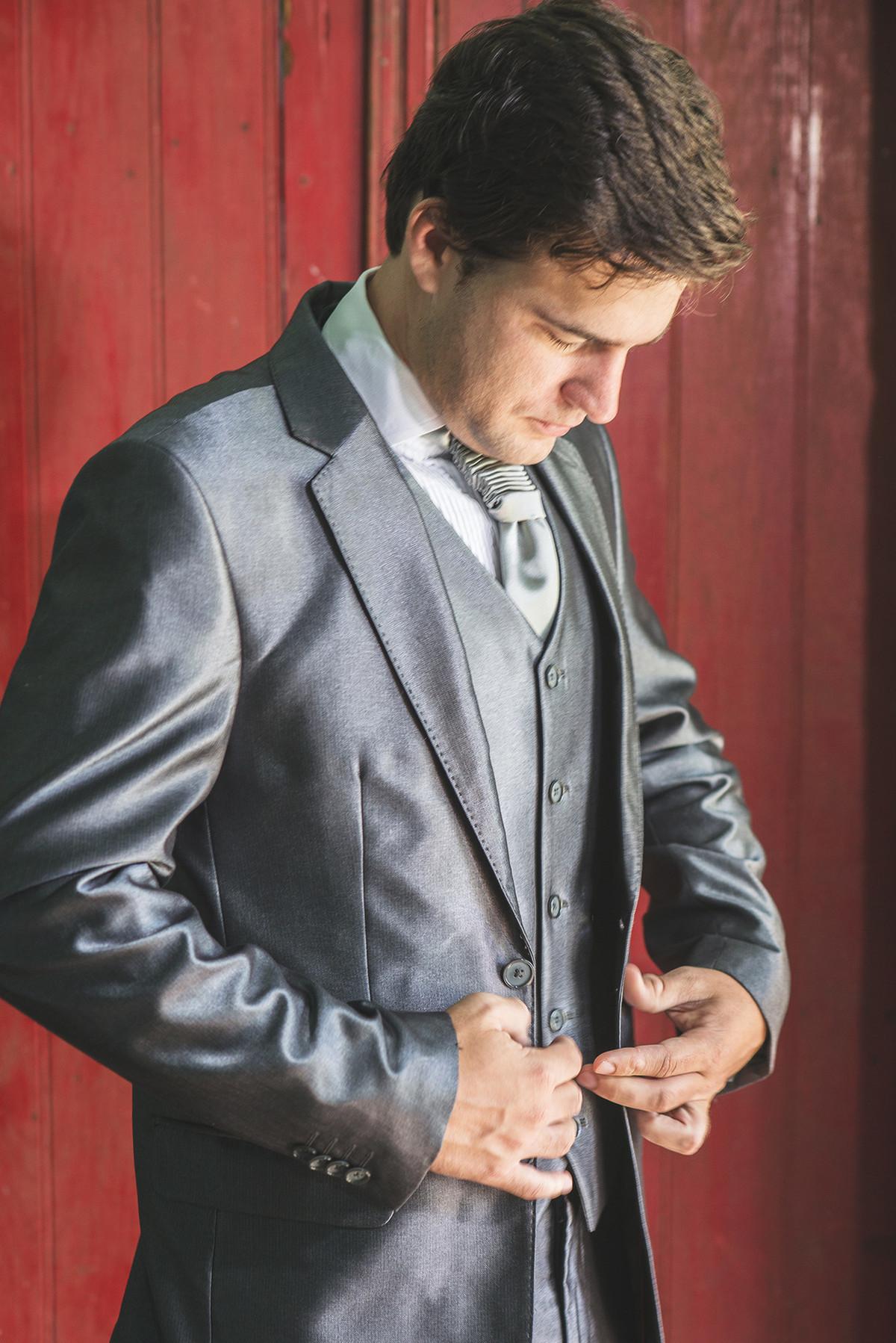 Detalhe do noivo abotoando a manga da camisa  para o casamento