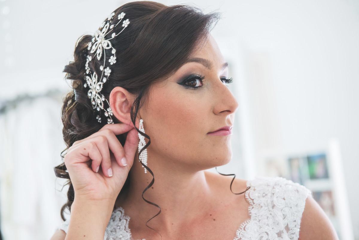 Noiva conferindo os últimos detalhes antes do casamento, olhando o brinco no espelho.