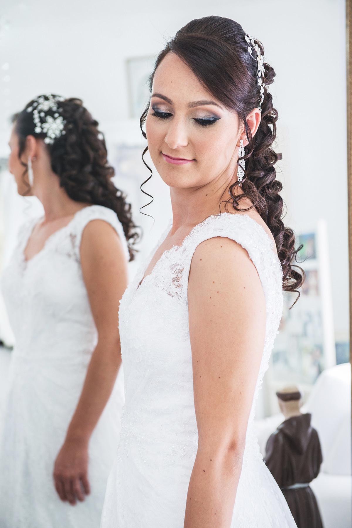 Noiva conferindo o vestido na frente do espelho antes da cerimônia de casamento.