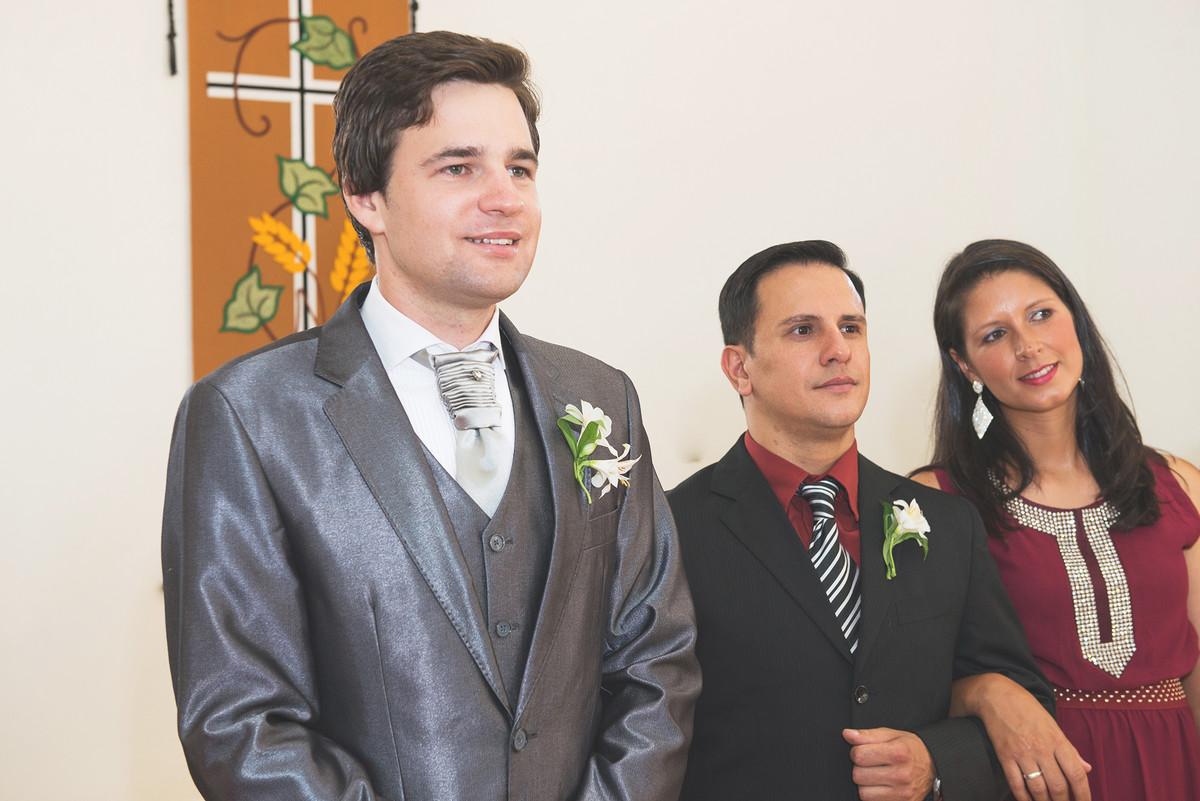 Sorriso do noivo ao ver a noiva entrando na igreja no momento do casamento.