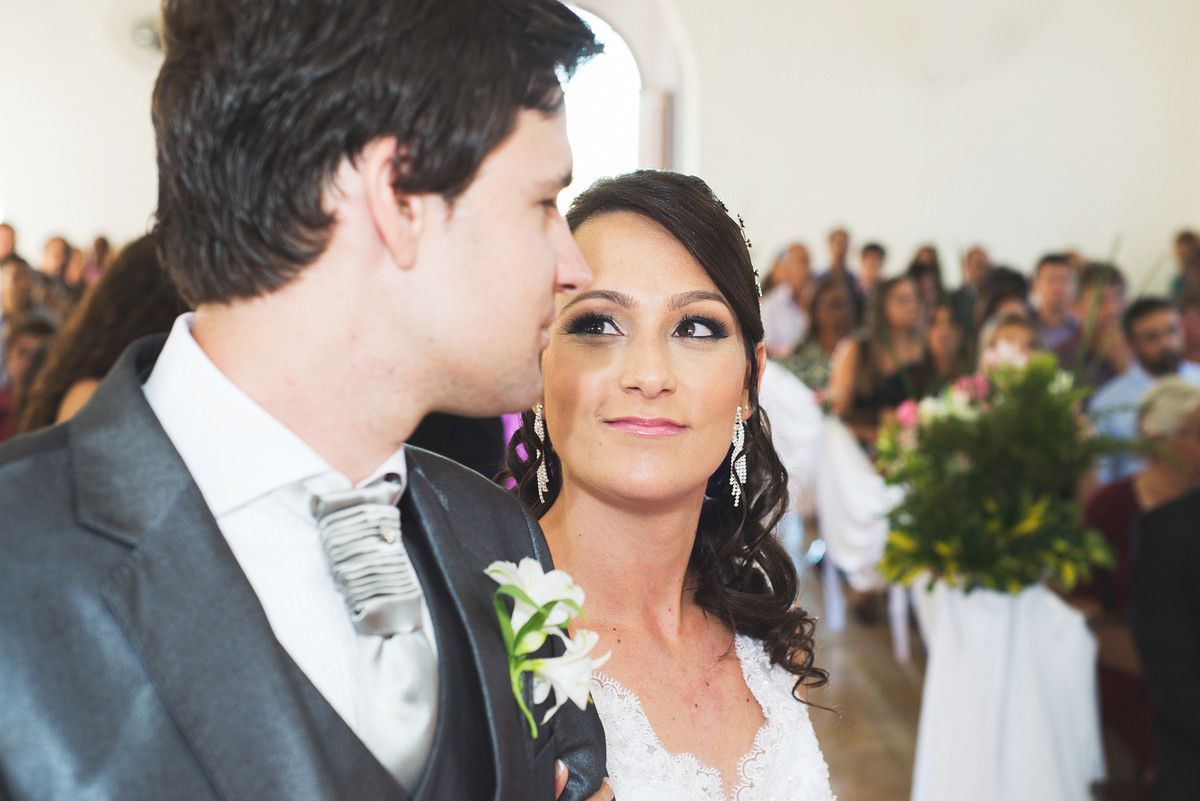 Noiva dando um olhar singelo para o noivo no momento da cerimônia de casamento.