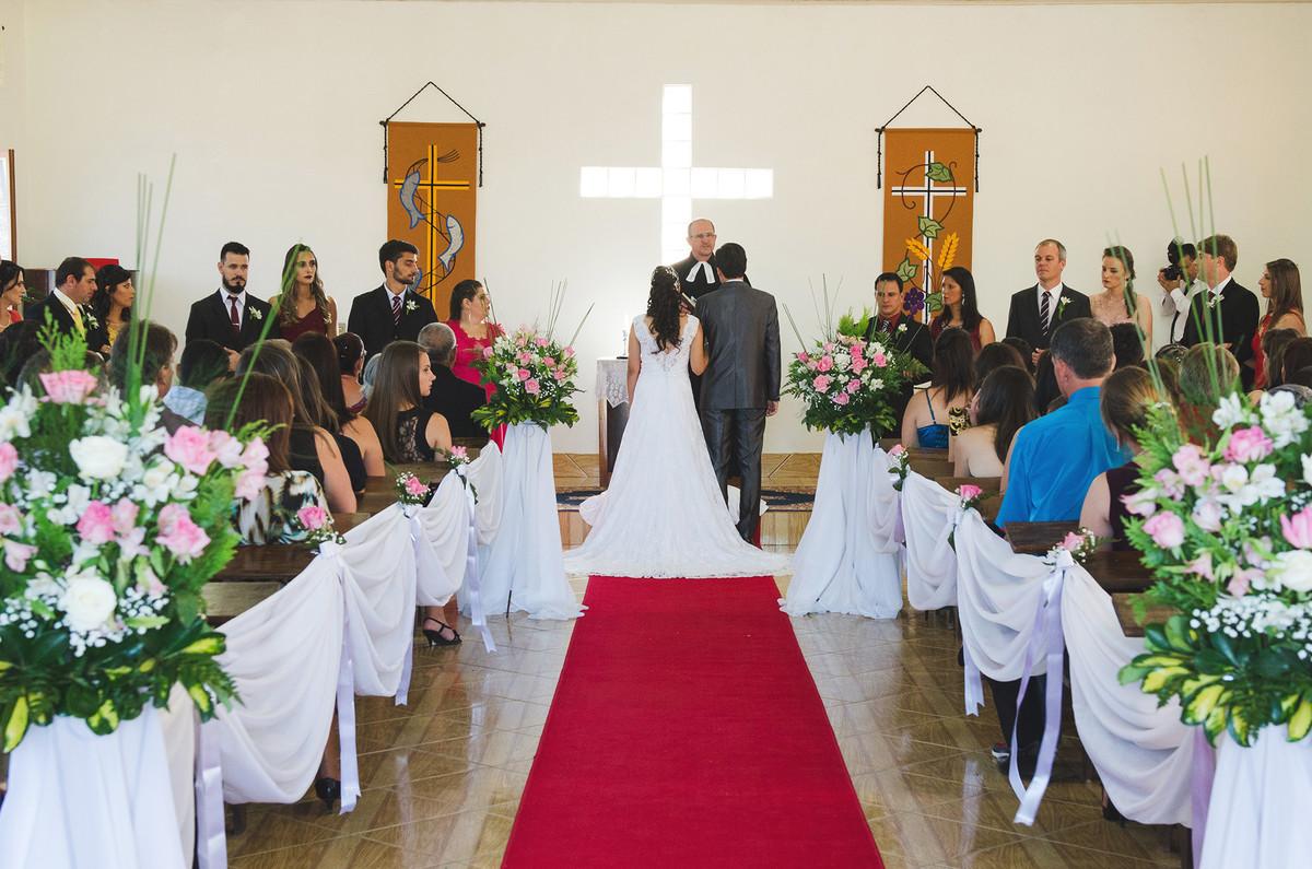 vista de dentro da igreja com noivos no altar durante o casamento.