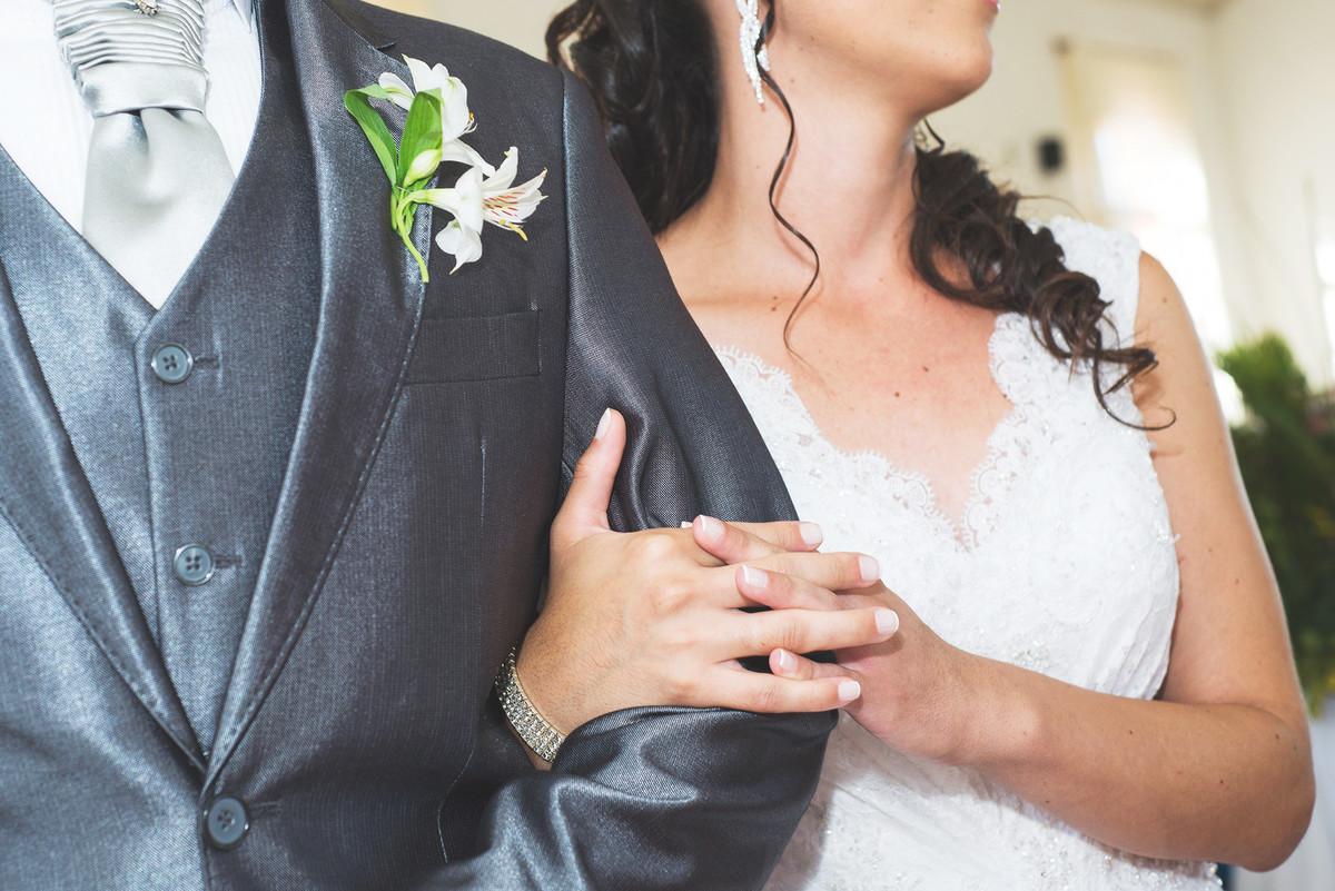 detalhe da noiva abbraçando o braço do noivo, detalhe das mãos.