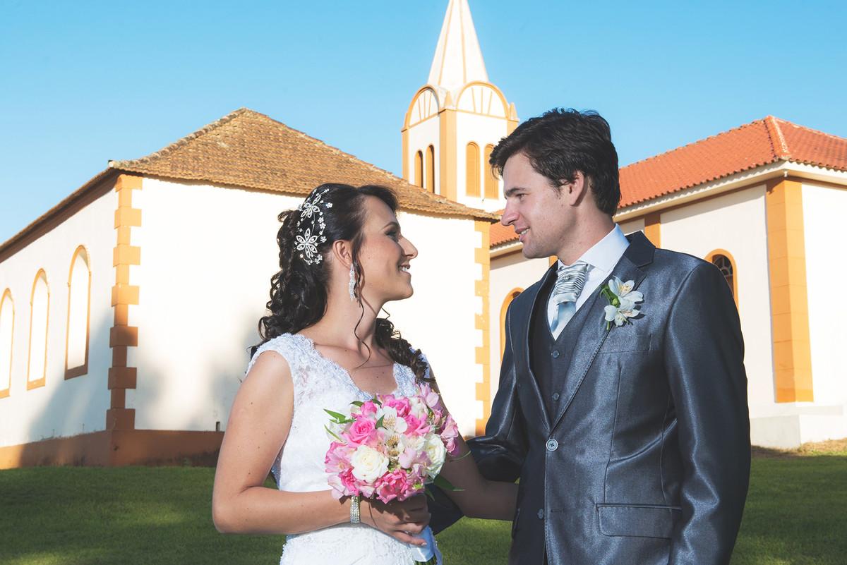 Fotos dos noivos com a igreja ao fundo.