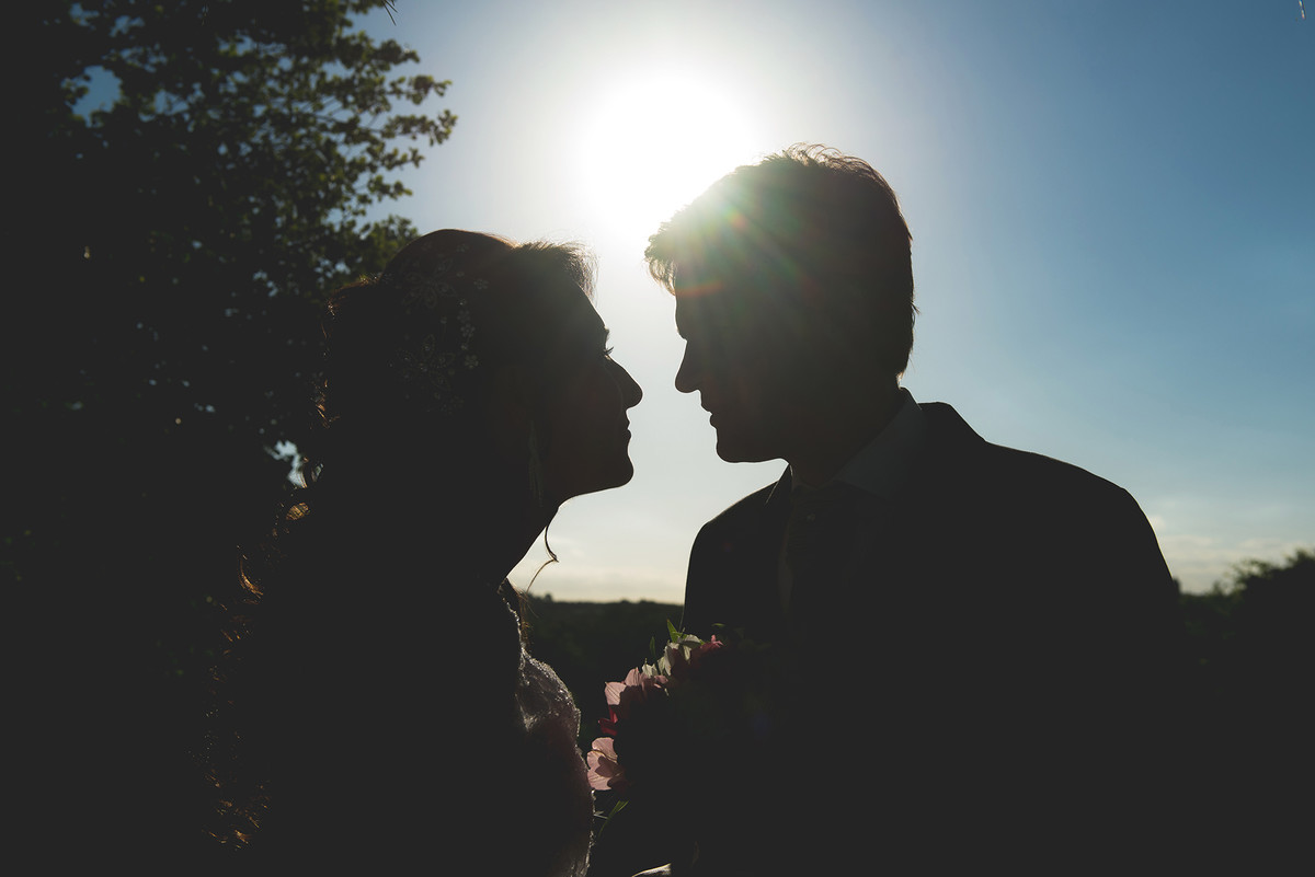 Foto contra a luz do casal de noivos.