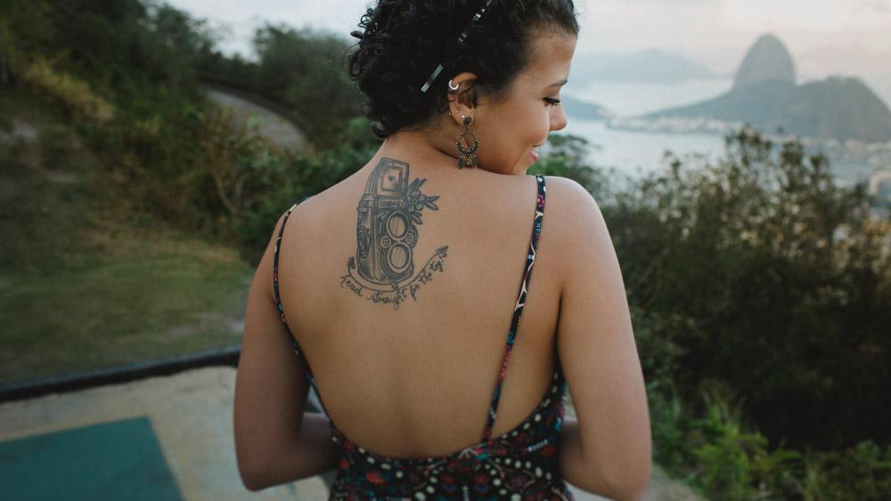 Ao fundo podemos ver o Pão de Açúcar, Nathalia posa meio tímida e deixa revelar Tattoo feita da sua xodó, uma RolleiFlex e o texto Head straight for the top!