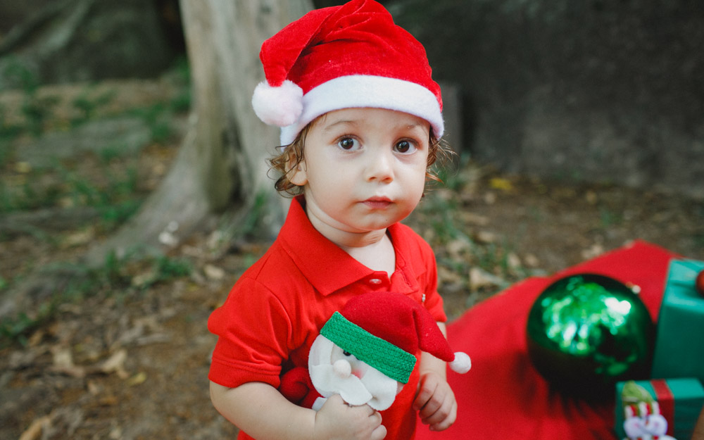 Antônio vestido de papai noel durante a sessão de fotos com Aline Lelles | Fotografia Afetiva | Fotografia de Criança | Fotografia de Bebê