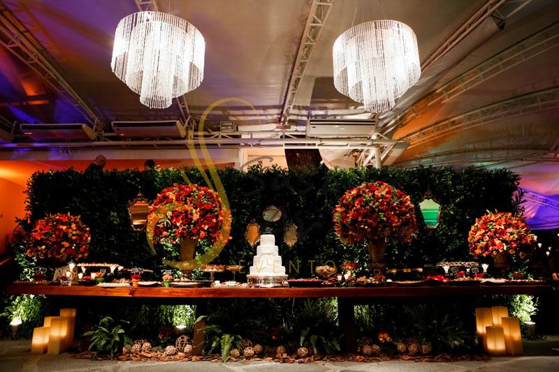 Casamento Zéfiro Niterói, mesa de doces e bolo. com flores vermelhas e laranja, muro inglës e lustres.