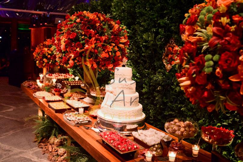 Casamento Zéfiro Niterói, mesa de doces  e bolo com flores aranja e vermelho.
