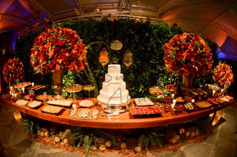 Casamento Zéfiro Niterói, mesa de doces e bolo com flores laranja e vermelho, paisagismo sob a mesa, muro inglês e espelhos.