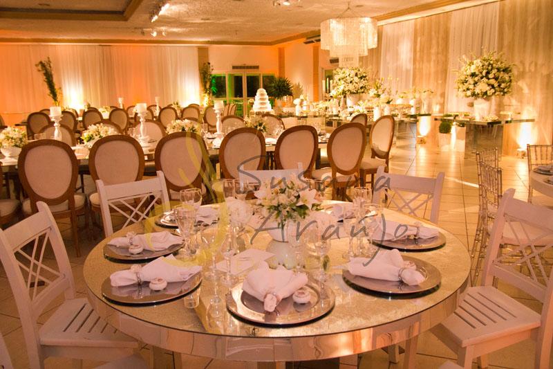 Decoração de casamento Solar Imperial, mesa de convidados de espelho com flores e arranjos de flores brancas. Composta com sousplat, guardanapos e taças