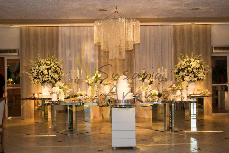 Decoração de casamento Solar Imperial, mesa de doces e bolo com flores e arranjos de flores brancas.