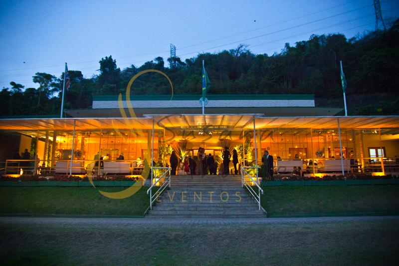 Casamento Rio Cricket Niterói, lounges com flores e arranjos de flores brancas, e mobiliário de madeira.