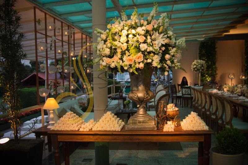 Arranjo de flores, bem casados, mesa de bem casados, Casamento Rio Cricket Niterói, mesa de bem casados com flores e arranjos de flores brancas e chá, e mobiliário de madeira.
