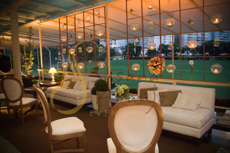 Velas, lounges, plantas, almofadas , plantas, Casamento Rio Cricket Niterói, lounges com flores e arranjos de flores brancas, e mobiliário de madeira. Velas suspensas, flores suspensas