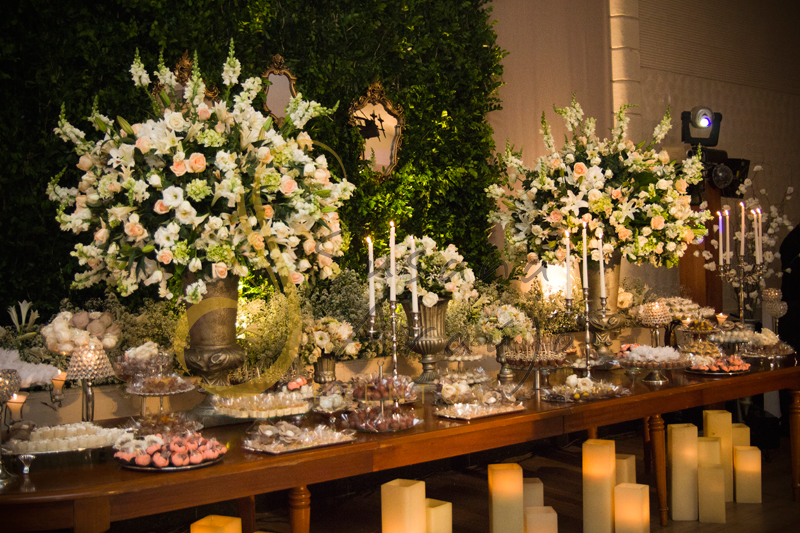 Casamento Rio Cricket Niterói, mesa de doces e bolo com flores e arranjos de flores brancas, e mobiliário de madeira.  Velas, castiçais, muro inglês e espelhos.
