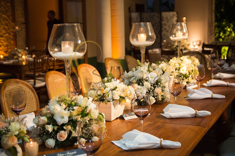 Velas, Flores, guardanapos, mesa de família, Casamento Rio Cricket Niterói, mesa de convidados com flores e arranjos de flores brancas e chá, e mobiliário de madeira.
