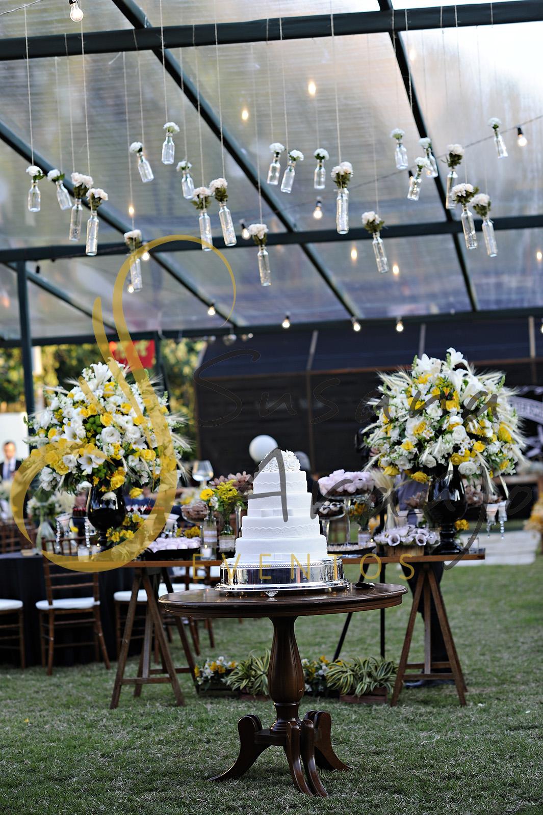 Casamento Cerimônia ao ar livre gramado sitio Decoração floral flores amarelas brancas mesa doces bolo arranjo alto decorativo flores suspensas vidrinhos