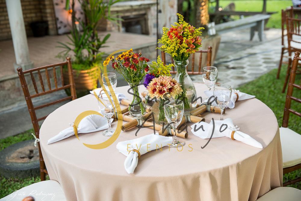 Casamento Cerimônia ao ar livre gramado sitio Decoração floral flores arranjinhos treliça bambu composição vidros centro mesa convidado flores laranja amarelo rosa toalha palha